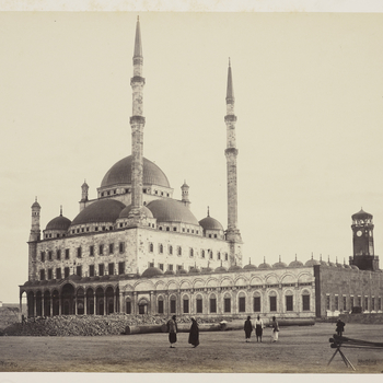 View of Mosque of Mohammed Ali in Cairo, Egypt. Alabaster building seen across square, with 2 tall minarets centre. Single row of columns supporting round arches lining court, left.