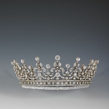 Tiara of diamonds and silver;  in two parts, both of which can be worn separately.   Of a scroll and festoon design in diamonds set on a detachable bandeau base of alternate circular and lozenge diamonds between two plain diamond bands.
