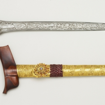 Sumatran kris and sheath. The pattern-welded iron blade is straight, with a dull pamir. The ivory hilt is of 'kingfisher' form, and is connected to the blade by a copper mendaq with a gold ring. The top of the wooden scabbard (wrangka) is plain, and the l