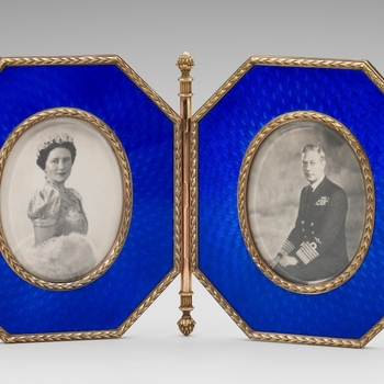 A Faberge double photograph frame, the two frames of octagonal shape of blue enamel. The frames of gold are joined by a hinge ending at the top and bottom in an acorn finial. The edge of the frames and oval reserves with laurel leaf border. Frames contain