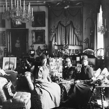 Photograph of Empress Marie Feodorovna of Russia (1847-1928), and Queen Louise of Denmark (1817-98), and Alexandra, Princess of Wales (1844-1925), all seated, surrounded by much furniture, including screens of photographs and framed photographs, in a sitt