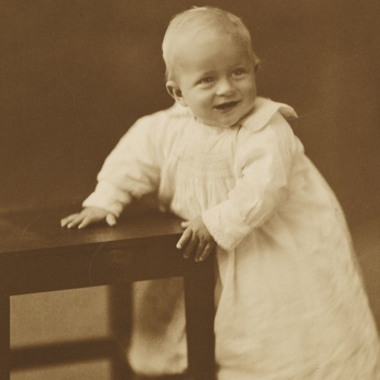 Photograph of the infant Prince Philip of Greece, later HRH The Duke of Edinburgh, aged approximately one year. He is pictured holding on to a wooden chair which he stands next to.