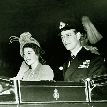 Photograph of Queen Elizabeth when Princess Elizabeth and The Duke of Edinburgh driving in an open carriage to Waterloo Station for the start of their honeymoon.
