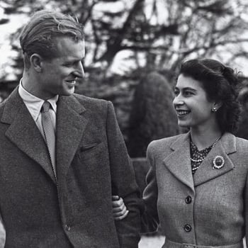 Photograph of a half length informal portrait of Princess Elizabeth (b. 1926), later HM Queen Elizabeth II standing on the right and HRH The Duke of Edinburgh (b. 1921) on the left. The couple face each other. Taken outside during their Honeymoon at Broad