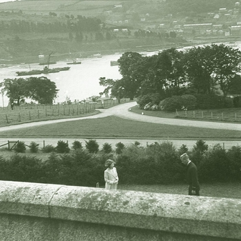 Negative of HRH Princess Elizabeth, later Queen Elizabeth II (b. 1926) meeting HRH Prince Philip (b. 1921) within the garden of the Captain's House, Dartmouth. Prince Philip wears Naval Lieutenant's uniform. Wall in foreground and harbour in the backgroun