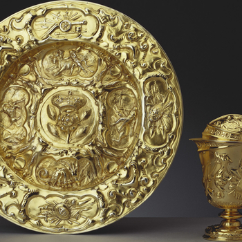 A silver-gilt basin embossed with military trophies. Four panels, on the inner rim of the basin, depict the Labours of Hercules.