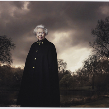 Photograph of HM Queen Elizabeth II standing in three-quarters length and facing the viewer. The Queen is set against a background featuring trees and clouds and she is pictured wearing the Admiral's Cloak.