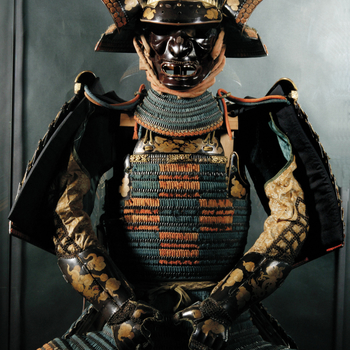 Full suit of Japanese armour [domaru]; brown and gold lacquer pieces linked with red and blue plaited silk ribbons. Comprising helmet, mask, shoulder pads, sleeves with gauntlets attached, thigh guards, shin guards, breast plate, back plate and skirt sect