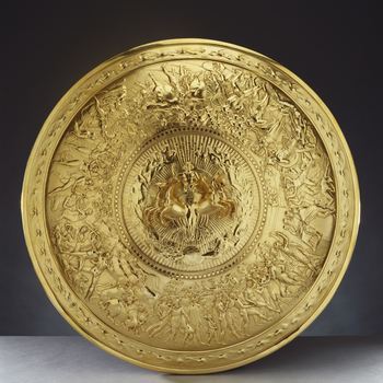 A silver-gilt convex shield with a central medallion cast in high relief showing Apollo in a quadriga, surrounded by stars and female figures representing the constellations. The broad border is cast in low relief with scenes of human life (a wedding and