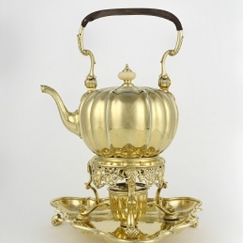 A silver gilt melon-shaped tea kettle and stand, with a bail handle with leather grip, a hinged lid with ivory knop handle and a swan-neck spout; the body is engraved with stylised strapwork. The stand, fitted with a burner, has a pierced apron and three