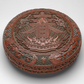 Large Imperial shallow box, with rounded sides and flanged rim, the matching cover with almost flat top. With many layers of ochre-yellow, green and red lacquer applied over a wood base. Carved on the top, a circular panel within a 'meander scroll&r