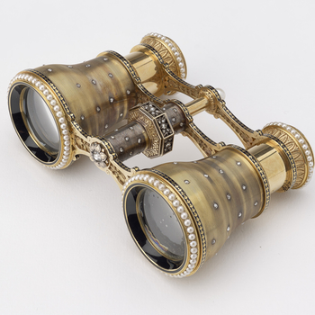 A pair of engine-turned gold opera glasses, scattered with diamonds and ringed with pearls at both the looking and viewing ends of each glass, the central hinge with a diamond-set octagonal twister and pearl finial. <br /><br />Tiffany & Co. were well