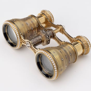 A pair of engine-turned gold opera glasses, scattered with diamonds and ringed with pearls at both the looking and viewing ends of each glass, the central hinge with a diamond-set octagonal twister and pearl finial. Tiffany & Co. were well known for t