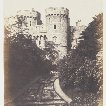 Photograph of the Norman Tower, taken from the Moat Garden, Windsor Castle. There are trees on either side of the garden.