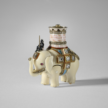 An ivory elephant with separate, jointed body legs and head, ridden by an enamel man sitting on its head and carrying a pink and white enamel castle with two  rose cut diamond set bands and a pierced upper rim, the top set with a