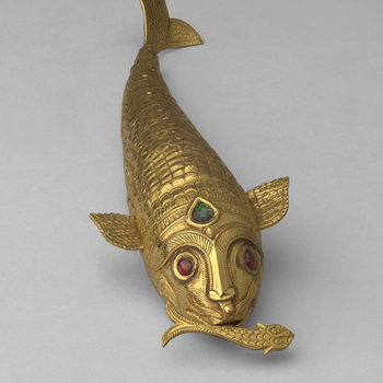 A flexible gold fish; ruby eyes and an emerald inserted in forehead; two small chased wing shaped fins and a scale pattern tail. Holding a smaller flexible fish in its mouth