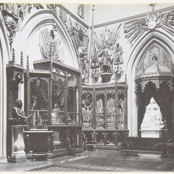 Photograph of theGrand Vestibule, with Boehm's statue of Queen Victoriawitha collie (RCIN 35336)under a wooden Gothic canopy. The walls are lined with Gothic display cabinets filled with mostly weapons; above them are displays of a