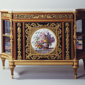 The cabinet, rectangular in shape, has incurving splayed sides lined in glass and divided by a shelf. It is supported on four fluted tulipwood peg-top feet. The single door in the front is flanked by ebony panels fitted with matching candelabrum mounts. T