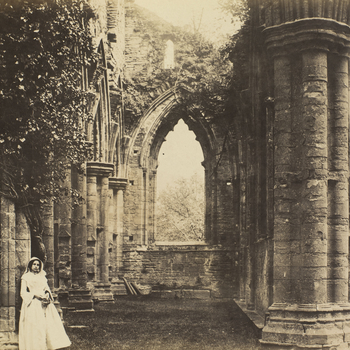Photograph of a young woman at Tintern Abbey. The woman stands in the foreground, on the left. She leans against anivy covered pillar and looks towards the camera. The view is of an aisle that stretches to the background of the photograph with a win