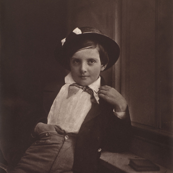 Photograph of a young boy wearing a tar hat and leaning back against a shelf on which also rests a small book. He has his right hand tucked into his trouser top and faces the viewer.