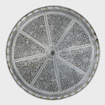 Round target ofiron, very slightly conical to the front and turned inwards over a wire around its edge. A series of thirty-eight iron rivets with domed brass caps and one empty rivet-hole follow the edge. The empty hole is situated at the centre of