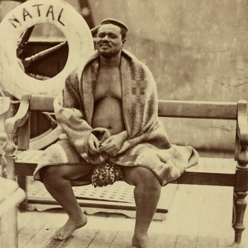 Photograph of Cetshwayo on board HMS Natal. He is sitting on a wooden bench with a lifebuoy marked 'NATAL' behind him to the left. He is wearing a fur loincloth and has a blanket wrapped around his shoulders. He has an isicoco, a band of hair and grass wo