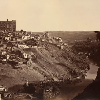 Photograph of the city of Toledo in Spain with buildings, including the Alcázar, populating the higher slopes of the city and the River Tagus flowing through the valley on the right.  The Alcázar was originally built as a Roman Palace before