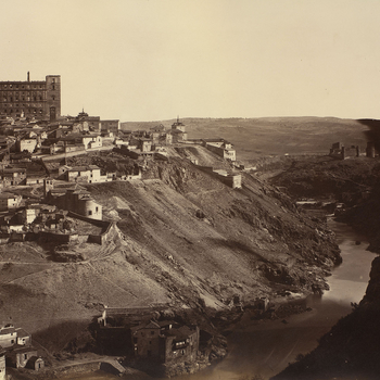 Photograph of the city of Toledo in Spain with buildings, including the Alcázar, populating the higher slopes of the city and the River Tagus flowing through the valley on the right. <br> <br>The Alcázar was originally built as a Roman Palac
