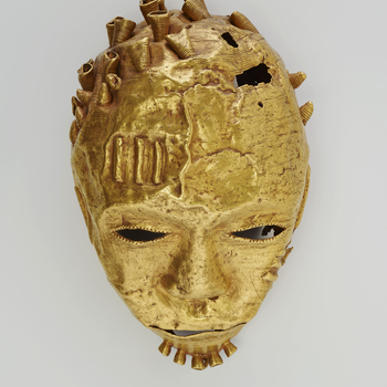 An Ashanti gold trophy head in the form of a hollow mask,with hammered facial features and pierced eyes, nostrils and mouth. Narrow strips of gold on the forehead and cheeks emulate scarification. Wirework coils, some missing,form hair curls a