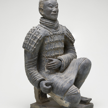 A kneeling Chinese warrior wearing body armour, his hair tied up in a bun and with a short moustache, sculpted in dark grey clay. The sculpture is a small-scale replica of the kneeling archerfrom the Terracotta Army of Emperor Qin Shi Huang (259-210