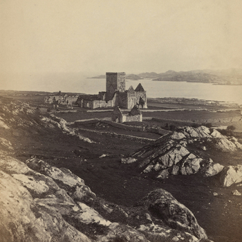 Photograph of the ruins of Iona Abbey situated on the Ross of Mull, a large peninsula on the Isle of Mull. In the foreground are large boulders. The central tower of the Abbey stands above the ruins of the nave and another ruined, smaller dwelling st
