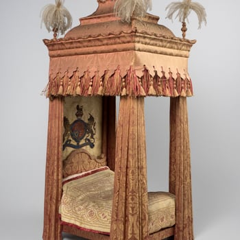 Miniature tester bed upholstered in pink and green silk. Tester with stepped canopy with feather plumes; deep fringed and tassled border. Silk back with applied Royal Coat of Arms. Shaped headboard. Drapes glued into folds. Quilt of pale gold and sil
