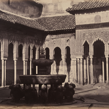 Photograph of the courtyard of Lions in the Alhambra Palace, Granada. A central fountain in the shape of a dodecagon carved from marble and supported on the backs of stone Lions, stands in the foreground. In the background, fine pillars support porticos w