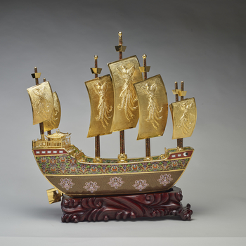 This is a model of the treasure ship sailed by the navigator and diplomat Zeng He of the Ming Dynasty. The prow of the ship is decorated with a dove and olive branch medallion, emblematic of peace, whilst the sides of the hull are decorated with elements