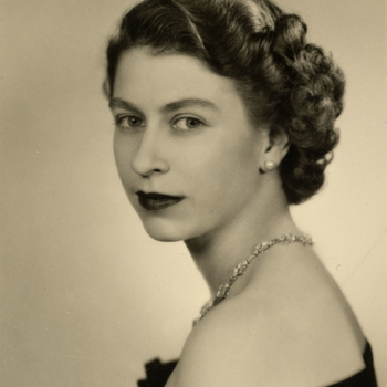 Head and shoulders portrait of HM Queen Elizabeth II, facing the viewer, her torso in left side profile. She wears a black taffeta evening dress with a diamond necklace.