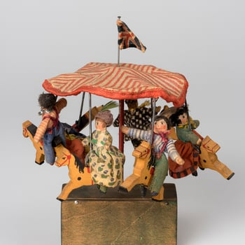 Miniature toy merry-go-round with red and white striped cotton canopy with Union flag; from which are suspended six wooden painted horses each with wooden and textile rider. On green painted wooden base containing mechanism and turning hand