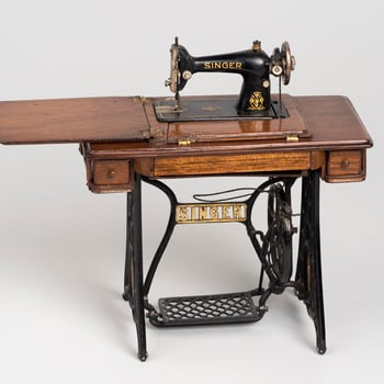 Miniature Singer sewing machine on integrated base of traditional form with hinged compartments (to lower machine), two small drawers and thread compartment at front.  Threaded for use.