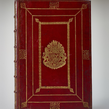 Bound in red calf, with coat of arms and motto of Queen Anne to centre, within panel design of roll of leaves and flowers in roundels, with floral lozenge-shaped tool to outer corners, within larger dogtooth roll panel, within larger frame of flowers in r