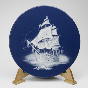 A Wedgwood circular ceramic plaque on blue ground with white slip image of the ship Victory at sea. As part of the commemorations of the 200th anniversary of the Battle of Trafalgar, The Queen attended a banquet on board HMS Victory at Southampton. This p