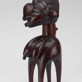 A carved wooden model headdress or Nimba, of the d'mba form found among the Baga people of Guinea. In the form of a stylised female, with four slender legs, pendulous breasts and an enlarged head with a long pointed nose and protruding chin. Headdresses o