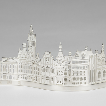 This tealight holder shows a condensed silhouette of the historic buildings in the city of Sheffield, for centuries a centre for metalwork including cutlery and silver. A tealight placed in the holder at the back would shine its light through the spaces c