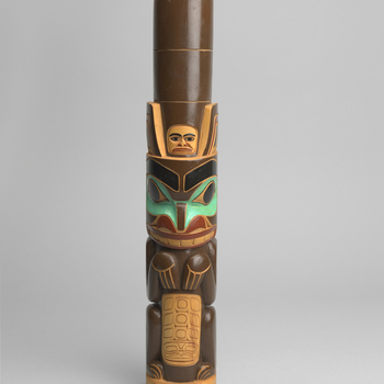 A totem pole carved with Canadian Northwest-Coast formline human and animal figures (a standing bear?), painted brown, green, red and black; the reverse is carved two-dimensionally with an orca and is signed and dated by the artist