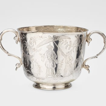 A silver two-handled cup on a shallow foot, with two scroll handles, the body flat chased with chinoiserie scenes, showing one figure holding a parasol over another, exotic birds and plants. The reverse is engraved in Latin: Ex Regio Fulcro