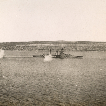 Photograph of HMS Queen Elizabeth under attack. The ship is at sea, the coast visible in the background. Two explosions cause large splashes in the water near the ship. The photograph was taken inside the Dardanelles on the same day the day HMS Bournet, H
