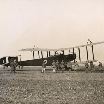 Photograph of Royal Flying Corps officers and airmen standing around a plane. In the cockpit of the plane sits Prince Albert, later King George VI (1895-1952). Photograph taken in Hendon.