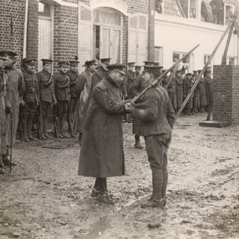 Photograph of King George V (1865-1936) in uniform and coat pinning amedal to the chest of a Sergeant from the 1st Division. The Sergeant holds arifle over his left shoulder. The action takes place on a muddy street lined with buildings. A lin
