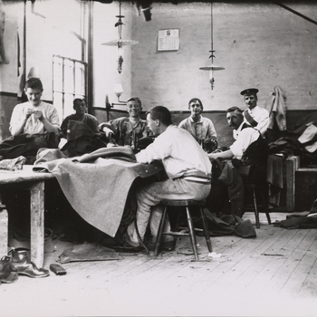 Photograph of Scots Guards at a tailors shop at the Chelsea Barracks. The soldiers are seated on stools around a large wooden table laid with sewing machines and various types of cloth. A selection of soldiers turn to face the camera and smile. A pile of
