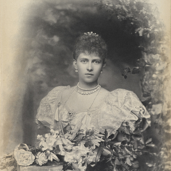 Photograph of a head and shoulder length portrait of Queen Sophia of Prussia (1870-1932) facing the camera, her body slightly angled to the left. She is framed by an arched structure featuring various fauna and poses in front of a flower arrange