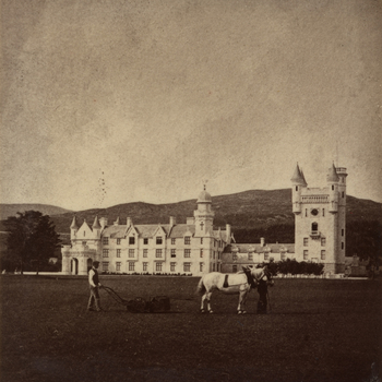 Photograph of two men in front of the new Balmoral Castle, Aberdeenshire.One leads a horse that pulls a lawnmower that the second man walks behind.
