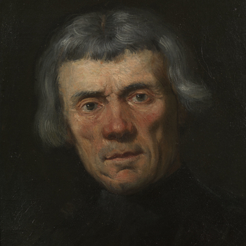 Head and shoulders portrait of a man, seen frontally, the head slightly inclined to the left, looking at the spectator. He has greying hair cut at the level of the ears, with a fringe.